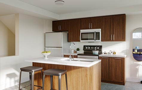 An interior shot of the Jasmine Infusion Terrace Home model shows off its brightly-lit kitchen and island.