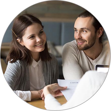 A young couple meet with their financial advisor to sign a mortgage contract.