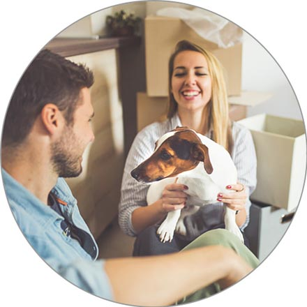 A young smiling couple and their Jack Russell Terrier sit on the floor of their new kitchen, surrounded by boxes.