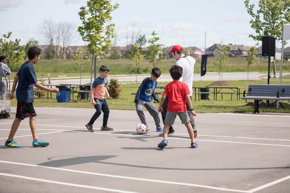 Kids playing soccer on a court in Orléans. List of the best parks in Orléans near Avalon.