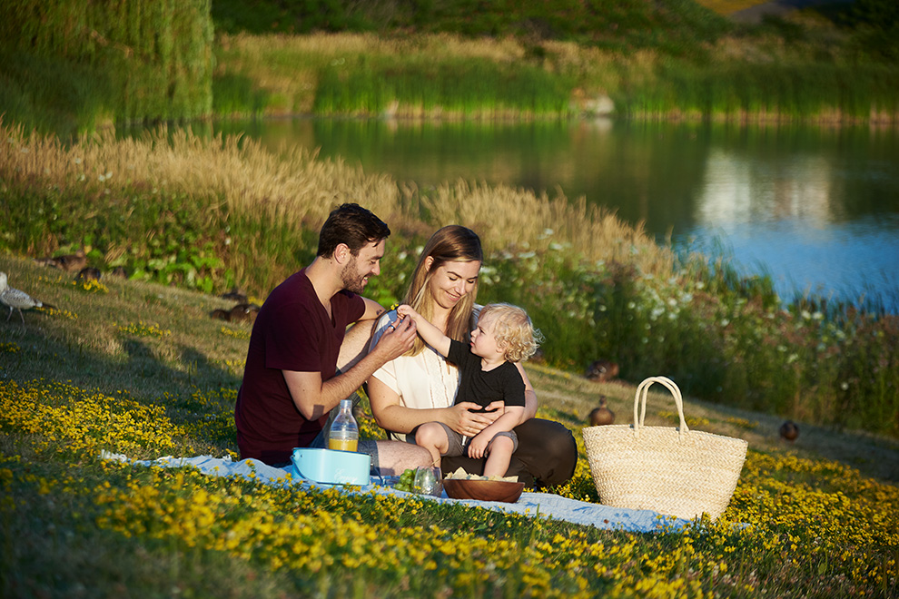 Young family having a picnic beside a lake. New release of homes for sale at Avalon Aquaview, Minto Communities.