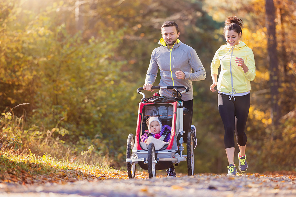 Couple and young child in a running stroller out for a run. Things to do in Barrhaven near Quinn's Pointe.