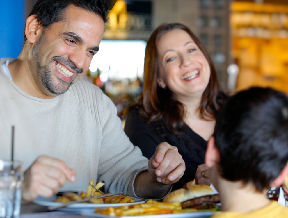 Family eating dinner at a restaurant. 7 reasons to choose Harmony in Barrhaven.