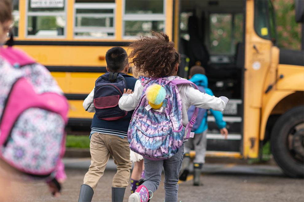 Photo of kids running to the bus