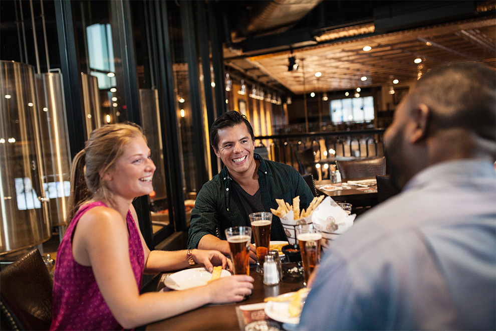 Friends enjoying beer at a restaurant in Kanata. 5 great spots to dine in Kanata.