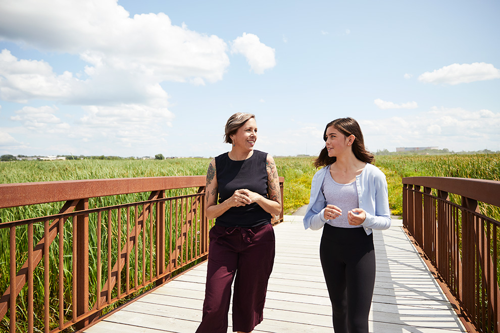 Mother & daughter walking in park in Kanata. New home designs coming to Kanata, winter 2020. Arcadia by Minto Communities.