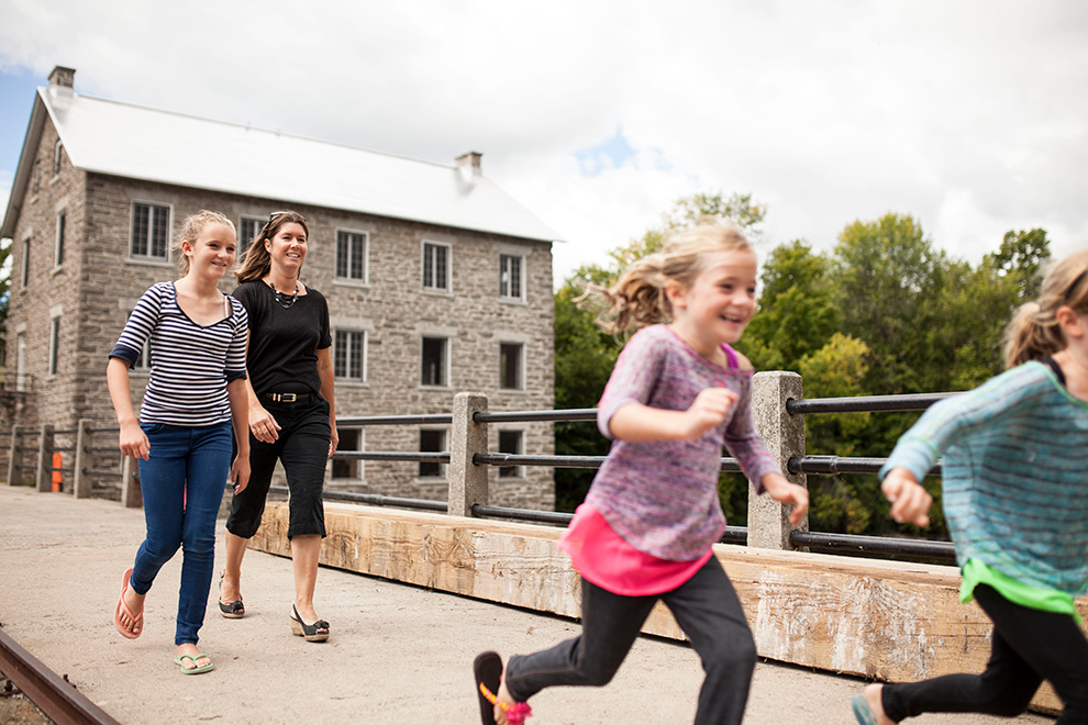 Mother and three daughters walking over bridge. Lifestyle in Mahogany, Manotick.