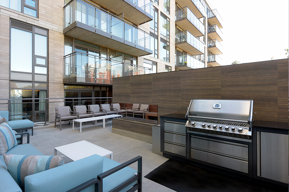 The shared outdoor patio space with loungers and a barbecue at Minto Beechwood.