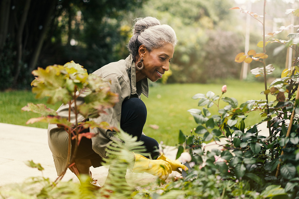 A retired woman tends to her home garden in the sunshine.