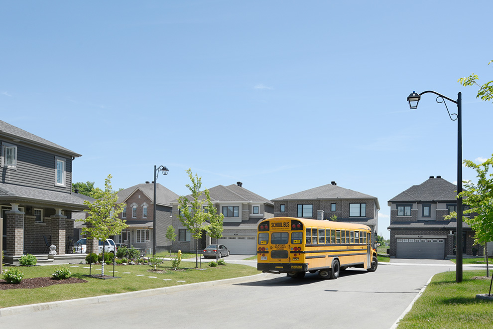 A school bus drives through the sunny streets of Quinn's Pointe.
