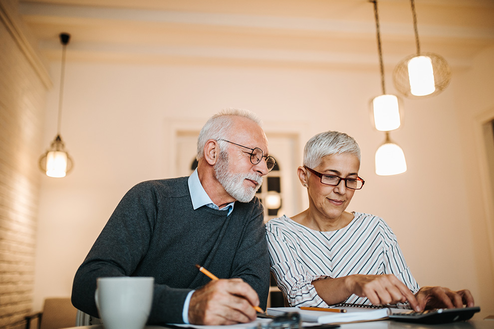 An elderly couple smile as they sit together and go over their finances.