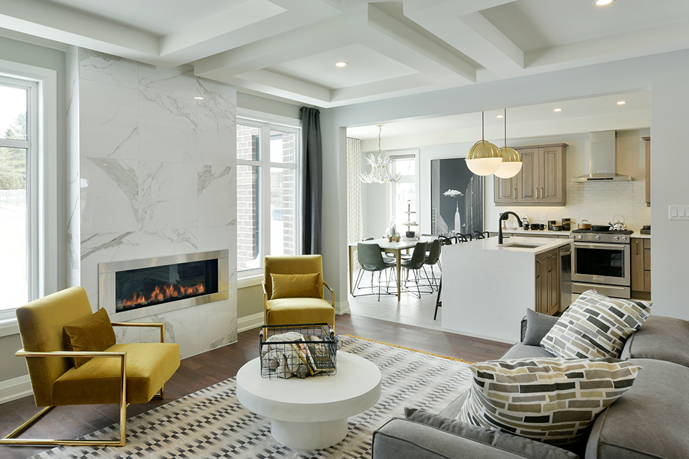 An interior shot of the Elderberry Single Family Home showing the stylish great room and marble fireplace feature and the adjoining open-concept kitchen.