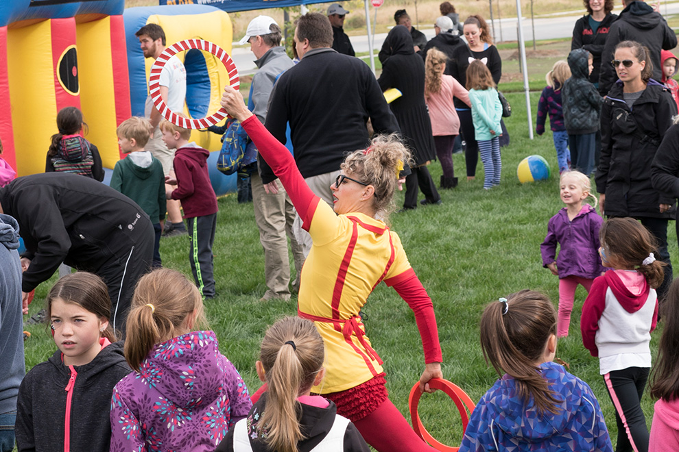 A performer entertains a crowd of onlooking children at a Minto Park Party in Avalon Encore, Orléans.