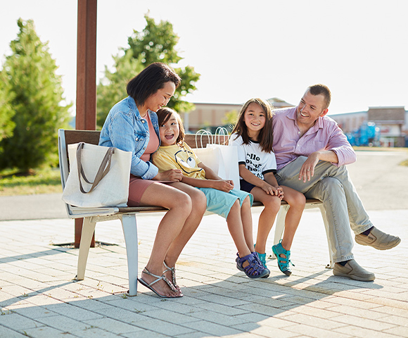 Photo of Family Sitting Outside Tanger Outlets in Kanata