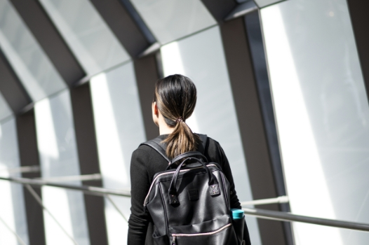 Woman walking with backpack. New condos for sale at Church & Adelaide. The Saint by Minto Communities