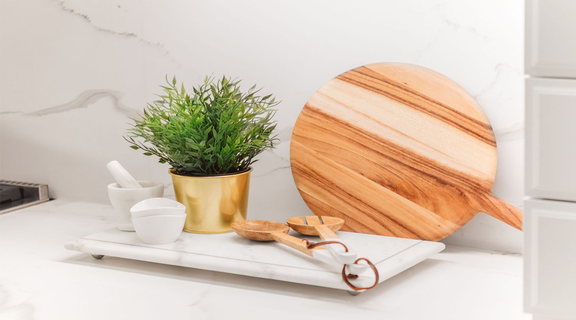 A cutting board, mortal and pestle and a plant on a kitchen counter.
