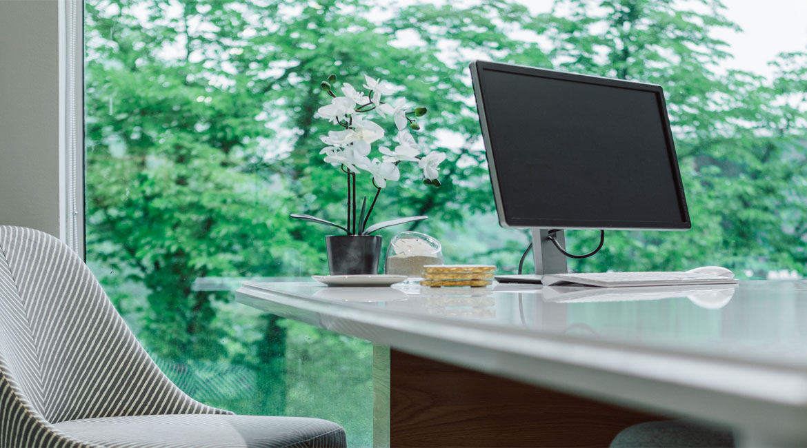 An orchid on a desk next to a computer.