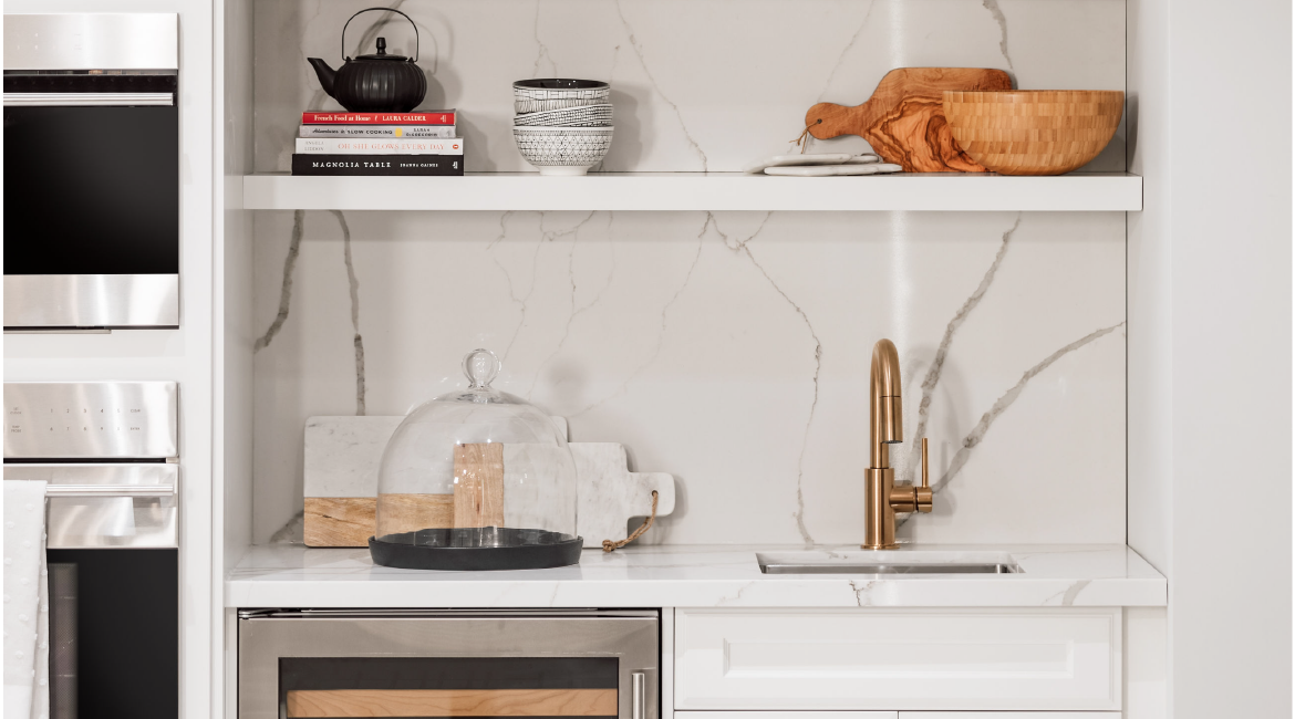 A kitchen shelf with a kettle, some books and some bowls.