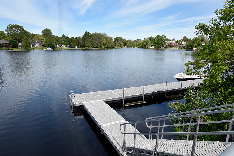 Dock with boat on lake in Mahogany, Manotick - a community built by Minto Communities