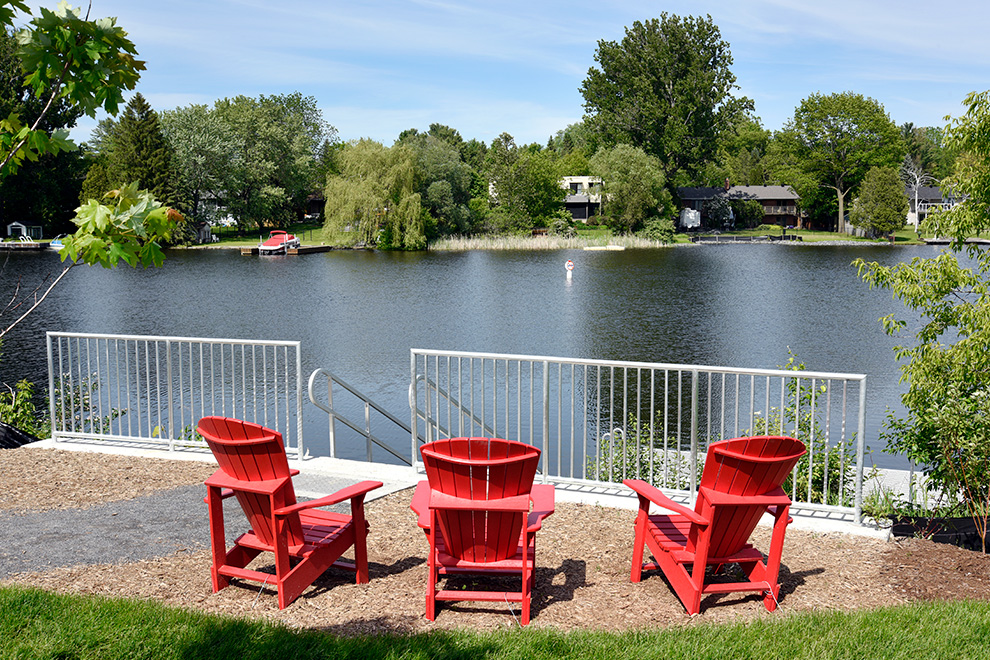 Red chairs overlooking water in Manotick - located near Mahogany, a community by Minto Communities