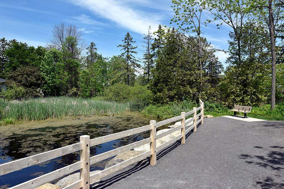A bench to sit near water in Manotick - located near Mahogany, a community by Minto Communities