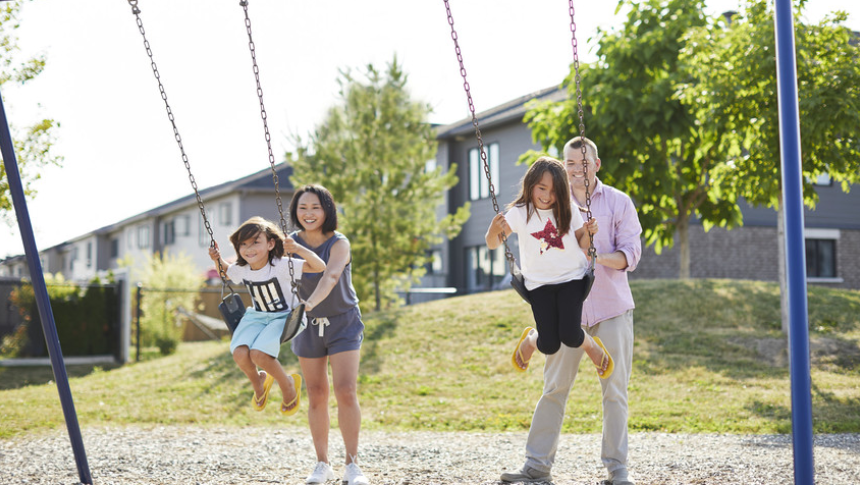 Parents pushing two little girls on swing in park in Arcadia, Kanata - a community by Minto Communities