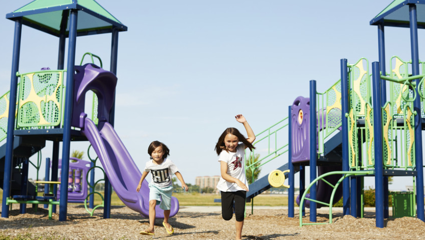 Two little girls running happily through park in Arcadia, Kanata - a community by Minto Communities