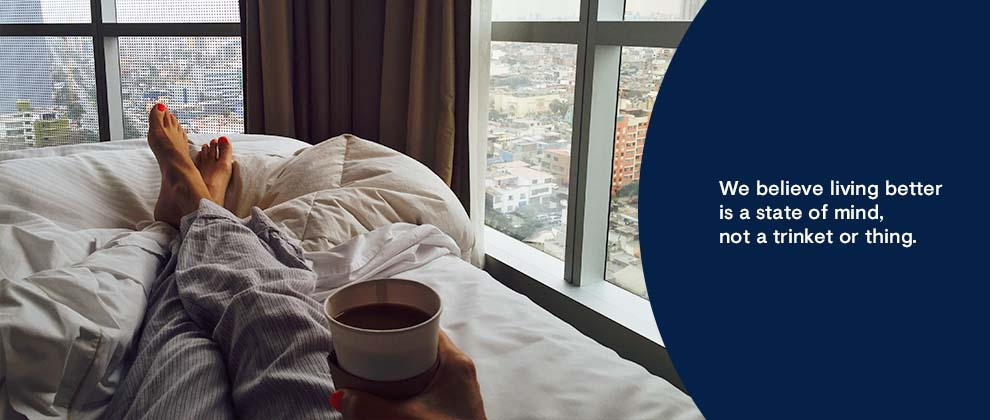 person in bed with coffee looking out window at city views