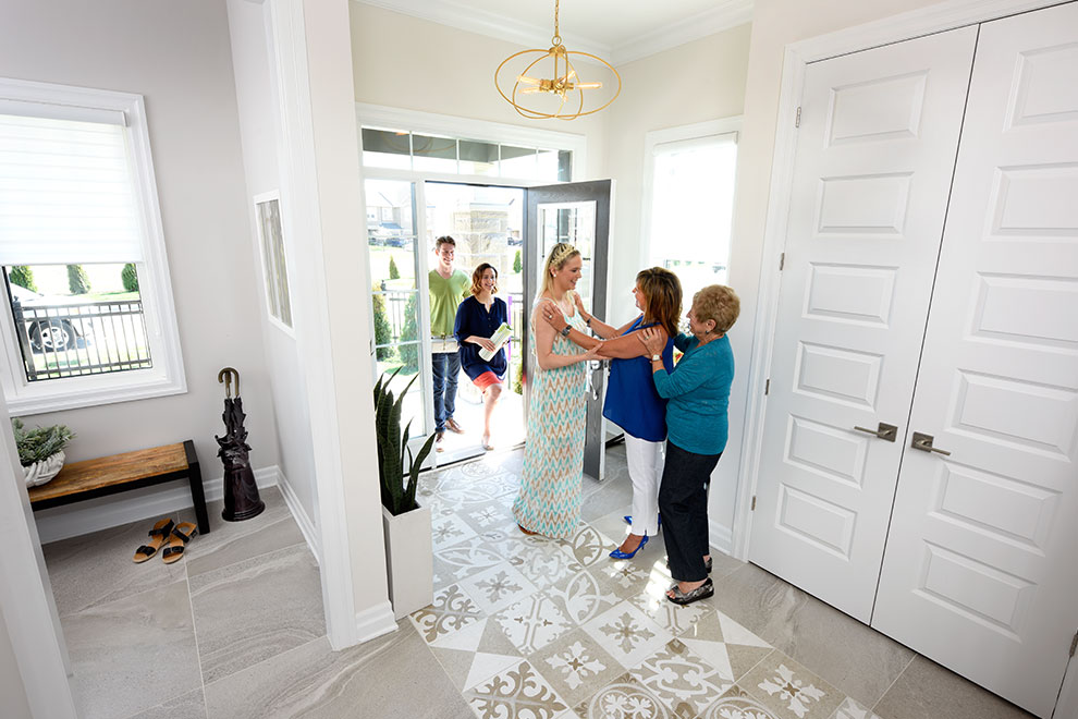 Family greeting guests in Marquette foyer, Minto Communities Ottawa