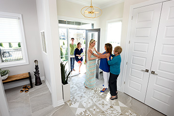 Family smiling and entering Marquette entry way - by Minto Communities